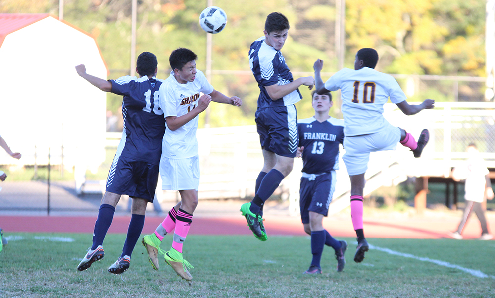 Sharon's Michael Baur (left) goes up for a header in the second half against Franklin. (Ryan Lanigan/HockomockSports.com)