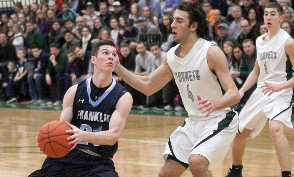 Franklin's Paul Mahon (left) drives to the basket against Mansfield's Sam Goldberg in the first half. (Ryan Lanigan/HockomockSports.com)