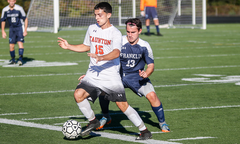 Taunton's Alec Nunes dribbles past Franklin's Andrew DiLeo in the first half. (Ryan Lanigan/HockomockSports.com)