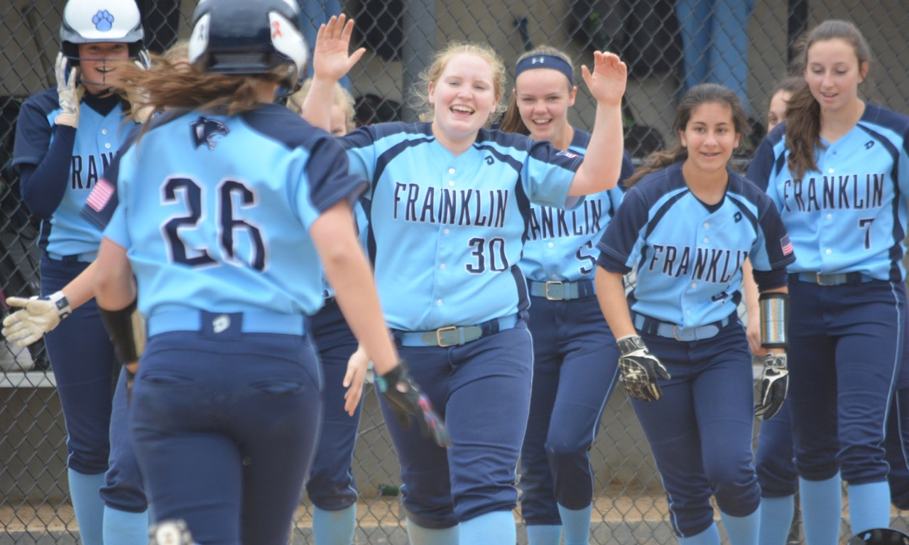 Franklin players race to celebrate with senior Meg Caron (26) after she drove in the game-winning run in the 10th inning to beat North Attleboro and keep Franklin's chance to reach the tournament alive. (Josh Perry/HockomockSports.com)