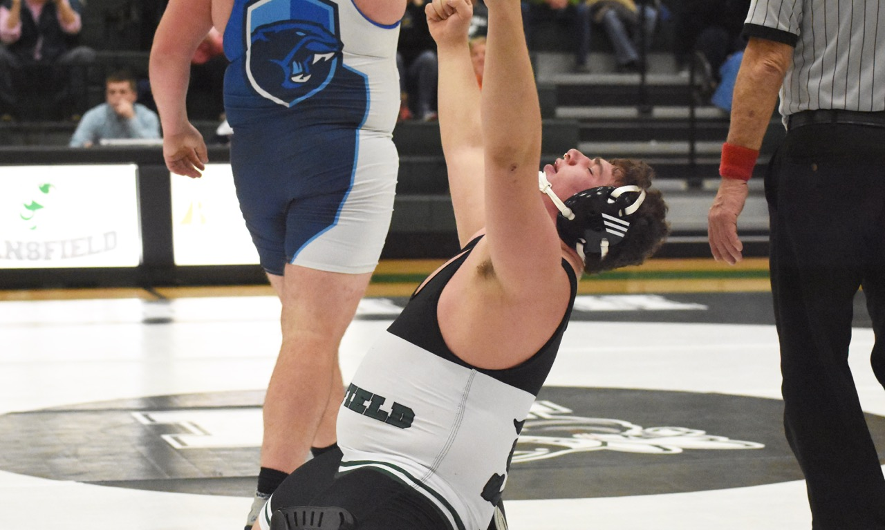 Mansfield junior Noah Jellenik lifts his arms to the rafters after his match at 285 pounds, Despite a loss in his individual match, Jellenik sealed a 30-27 win for the team that puts the Hornets on the brink of a first-ever league title. (Josh Perry/HockomockSports.com)