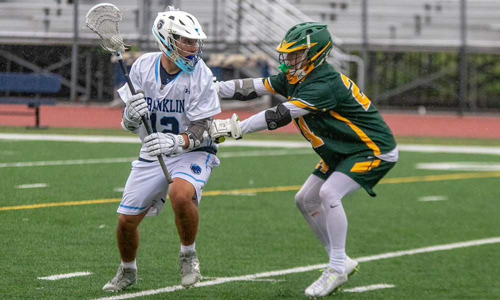 Franklin junior Owen Palmieri tries to get past the defense of King Philip's Aidan Bender in the second half. (Ryan Lanigan/HockomockSports.com)